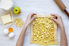 Μαγειρεύοντας πίτα ή strudel μήλων γυναικών στον άσπρο ξύλινο πίνακα, τοπ άποψη στοκ εικόνες