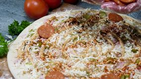 Μαγειρεύοντας πίτσα σαλαμιού αρχιμαγείρων, που φορά τα μαγειρεύοντας γάντια, foodporn έννοια Πλαίσιο Κλείστε επάνω για τα χέρια β φιλμ μικρού μήκους