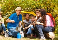 Μαγειρεύοντας σούπα αγοριών στο δοχείο για τους φίλους στη θέση για κατασκήνωση Στοκ εικόνα με δικαίωμα ελεύθερης χρήσης