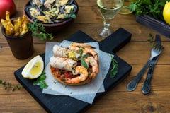 μαγειρεύοντας συστατικά ιταλικά τροφίμων Bruschetta με το καλαμάρι και τις γαρίδες, ντομάτες, μαϊντανός Στοκ Εικόνες