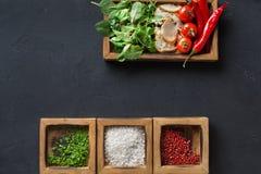 Μαγειρεύοντας συστατικά και χορτάρια στο ξύλινο κιβώτιο στο σκοτεινό υπόβαθρο Στοκ Εικόνες