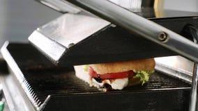 Μαγειρεύοντας το σάντουιτς σε μια ηλεκτρική σχάρα σε ένα εστιατόριο γρήγορου φαγητού, κλείστε επάνω την άποψη απόθεμα βίντεο