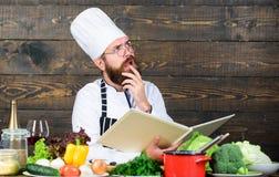 Μαγειρεύοντας τρόφιμα αρχιμαγείρων ατόμων γενειοφόρα Διαβασμένες τύπος συνταγές βιβλίων Μαγειρική έννοια τεχνών Το άτομο μαθαίνει στοκ φωτογραφία με δικαίωμα ελεύθερης χρήσης