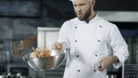 Μαγειρεύοντας τρόφιμα αρχιμαγείρων με το κάψιμο της πυρκαγιάς σε σε αργή κίνηση Αρχιμάγειρας που ρίχνει τα τρόφιμα φιλμ μικρού μήκους