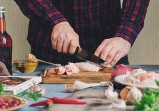 Μαγειρεύοντας φτερά κοτόπουλου ατόμων με τη σάλτσα των βακκίνιων στην εγχώρια κουζίνα Στοκ Φωτογραφία