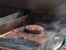 Μαγειρεύοντας χάμπουργκερ στη σχάρα και τον καπνό γύρω Στοκ εικόνα με δικαίωμα ελεύθερης χρήσης