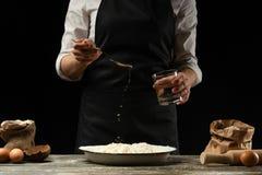 μαγειρική Ο μάγειρας μαγειρεύει τη ζύμη για τα ζυμαρικά, πίτσα, ψωμί Χύστε το νερό στο αλεύρι Εύγευστα τρόφιμα, συνταγές, μαγείρε στοκ εικόνες