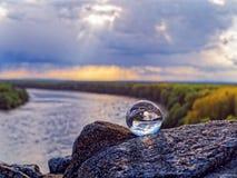 Μαγική σφαίρα γυαλιού στις παλαιές πέτρες Στο υπόβαθρο είναι η κάμψη του ποταμού, του δασικού και νεφελώδους ουρανού άνοιξη Στοκ Φωτογραφία