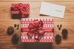 Μαγικοί υπόβαθρο θέματος Χριστουγέννων, παρόν, κώνοι πεύκων και κάρτα Χριστουγέννων στον ξύλινο πίνακα Στοκ Εικόνα