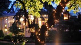 Μαγικό βίντεο νύχτας υποβάθρου ενός δέντρου με τη γιρλάντα και των φαναριών κοντά στο εστιατόριο απόθεμα βίντεο