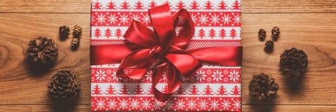 Μαγικό υπόβαθρο θέματος Χριστουγέννων, παρόν Χριστουγέννων και κώνοι πεύκων στον ξύλινο πίνακα Έμβλημα Ιστού Χριστουγέννων στοκ φωτογραφίες με δικαίωμα ελεύθερης χρήσης
