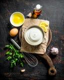 Μαγιονέζα σε έναν πίνακα κοπής με τα πράσινα, τα αυγά και το έλαιο στοκ φωτογραφία με δικαίωμα ελεύθερης χρήσης