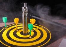 Μαγνητικά βέλη βελών και ηλεκτρονικό τσιγάρο μέσα στον ατμό στον κίτρινο πίνακα βελών Στοκ Εικόνες