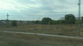 Μαγνητοσκόπηση από το παράθυρο ενός κινούμενου τραίνου Ρωσικό τοπίο φθινοπώρου: χωριό, τομείς, δάση, φύτευση, ουρανός απόθεμα βίντεο