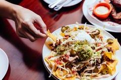 Μαζεψτε με το χέρι τη σαλάτα Nacho με το τεμαχισμένο λάχανο, το παστωμένο τσίλι, τη σέσουλα του αβοκάντο και το τυρί ντύνοντας με Στοκ φωτογραφίες με δικαίωμα ελεύθερης χρήσης