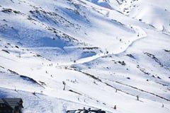 Μαζική κάθοδος των σκιέρ βουνών από μια ευρεία βουνοπλαγιά στοκ φωτογραφία με δικαίωμα ελεύθερης χρήσης
