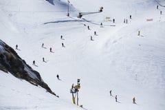 Μαζική κάθοδος των σκιέρ βουνών από μια ευρεία βουνοπλαγιά στοκ φωτογραφία