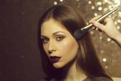 Μαθήματα για τη σύνθεση μοντέρνη θέτοντας γυναίκα κορίτσι που παίρνει τη σκόνη στο δέρμα προσώπου με τη βούρτσα makeup Στοκ εικόνες με δικαίωμα ελεύθερης χρήσης