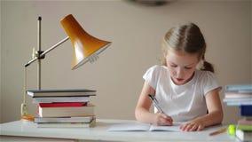 Μαθήματα εκμάθησης κοριτσιών, χαριτωμένο κορίτσι που κάνουν την εργασία της, μαθητριών στο σπίτι στον πίνακα απόθεμα βίντεο