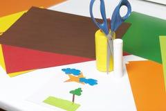 Μαθήματα στο applique Απαραίτητα στοιχεία: η κόλλα, το χρωματισμένα έγγραφο και το ψαλίδι βρίσκονται στην άσπρη επιφάνεια του πίν Στοκ Φωτογραφία