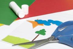 Μαθήματα στο applique Απαραίτητα στοιχεία: η κόλλα, το χρωματισμένα έγγραφο και το ψαλίδι βρίσκονται στην άσπρη επιφάνεια του πίν Στοκ Εικόνες