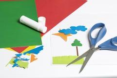 Μαθήματα στο applique Απαραίτητα στοιχεία: η κόλλα, το χρωματισμένα έγγραφο και το ψαλίδι βρίσκονται στην άσπρη επιφάνεια του πίν Στοκ Φωτογραφίες