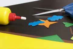 Μαθήματα στο applique Απαραίτητα στοιχεία: η κόλλα, το χρωματισμένα έγγραφο και το ψαλίδι βρίσκονται στη σκοτεινή επιφάνεια του π Στοκ Φωτογραφία