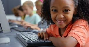 Μαθήτρια αφροαμερικάνων πλάγιας όψης που χρησιμοποιεί τον προσωπικό υπολογιστή γραφείου στο γραφείο στην τάξη 4k απόθεμα βίντεο