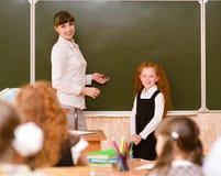 Μαθήτρια και δάσκαλος κοντά σε έναν σχολικό πίνακα Στοκ εικόνα με δικαίωμα ελεύθερης χρήσης