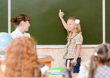 Μαθήτρια και δάσκαλος κοντά σε έναν σχολικό πίνακα Στοκ Εικόνα