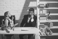 Μαθήτρια και μπαμπάς με το ακριβές και κουρασμένο βιβλίο λαβής προσώπων Στοκ φωτογραφίες με δικαίωμα ελεύθερης χρήσης
