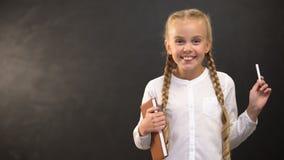 Μαθήτρια με το βιβλίο και το κομμάτι της κιμωλίας που χαμογελά στη κάμερα ενάντια στον πίνακα φιλμ μικρού μήκους