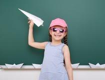 Μαθήτρια με το παιχνίδι αεροπλάνων εγγράφου κοντά σε έναν πίνακα, κενό διάστημα, έννοια εκπαίδευσης Στοκ Εικόνες