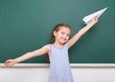Μαθήτρια με το παιχνίδι αεροπλάνων εγγράφου κοντά σε έναν πίνακα, κενό διάστημα, έννοια εκπαίδευσης Στοκ Εικόνα