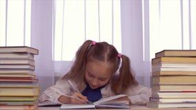 Μαθήτρια που έχει την ιδέα και που γράφει στο copybook Κορίτσι που κάνει την εργασία με τα βιβλία απόθεμα βίντεο