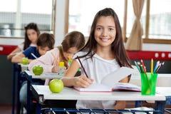 Μαθήτρια που γράφει στο βιβλίο στην τάξη στοκ εικόνες με δικαίωμα ελεύθερης χρήσης