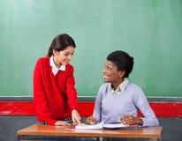 Μαθήτρια που δείχνει σε χαρτί κοιτάζοντας δασκάλων στοκ φωτογραφίες