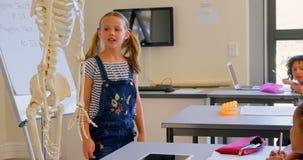 Μαθήτρια που εξηγεί το ανθρώπινο πρότυπο σκελετών στην τάξη 4k φιλμ μικρού μήκους