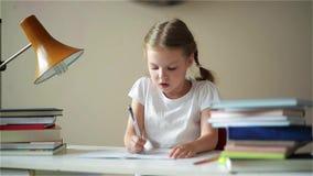 Μαθήτρια που κάνει την εργασία και που προετοιμάζεται για τους διαγωνισμούς, χαριτωμένα παιδιά που μαθαίνουν τα μαθήματά της απόθεμα βίντεο