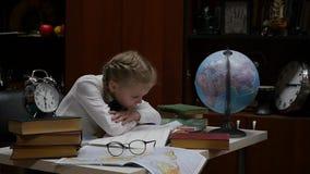 Μαθήτρια που κάνει την εργασία, λίγο ξανθό κορίτσι που στο σπίτι στον πίνακα εκπαίδευση παιδιών o απόθεμα βίντεο