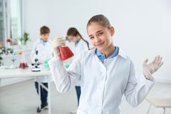 Μαθήτρια που κρατά την κωνική φιάλη στην κατηγορία στοκ εικόνα