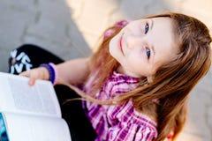 Μαθήτρια που μελετά υπαίθρια κοντά στο σχολείο στοκ φωτογραφία