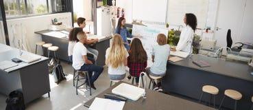 Μαθήτρια που παρουσιάζει μπροστά από την κατηγορία επιστήμης, υψηλή γωνία στοκ φωτογραφίες