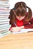 Μαθήτρια, schoolwork και σωρός των βιβλίων Στοκ εικόνες με δικαίωμα ελεύθερης χρήσης