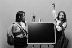 Μαθήτριες δίπλα στον πίνακα κιμωλίας στο ρόδινο υπόβαθρο Κορίτσια με τα έκπληκτα δάχτυλα λαβής προσώπων επάνω που έχουν την ιδέα  Στοκ εικόνα με δικαίωμα ελεύθερης χρήσης