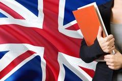 Μαθαίνοντας βρετανική γλωσσική έννοια Νέα γυναίκα που στέκεται με Ηνωμένη σημαία στο υπόβαθρο Βιβλία εκμετάλλευσης δασκάλων, στοκ εικόνα