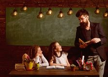 Μαθητές δασκάλων και κοριτσιών στην τάξη, πίνακας κιμωλίας στο υπόβαθρο Το άτομο με τη γενειάδα διδάσκει τις μαθήτριες, που διαβά στοκ φωτογραφία με δικαίωμα ελεύθερης χρήσης