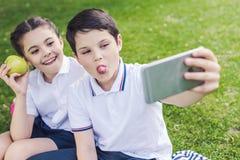 μαθητές που μορφάζουν και που παίρνουν selfie καθμένος στη χλόη στοκ φωτογραφίες