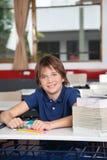Μαθητής με τα βιβλία και σφαίρα στο γραφείο Στοκ Εικόνα