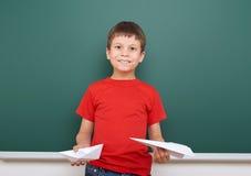 Μαθητής με το παιχνίδι αεροπλάνων εγγράφου κοντά σε έναν πίνακα, κενό διάστημα, έννοια εκπαίδευσης Στοκ φωτογραφία με δικαίωμα ελεύθερης χρήσης